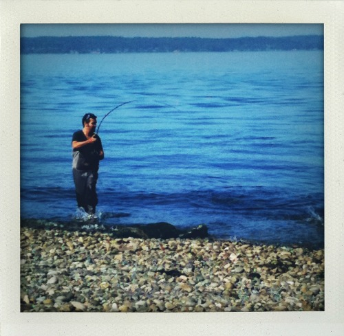 Reeling in his fourth fish of the day.